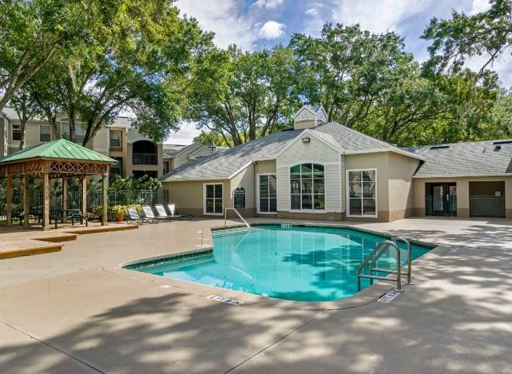 Swimming pool with lounge seating, shaded poolside picnic seating with apartment building exterior in the background