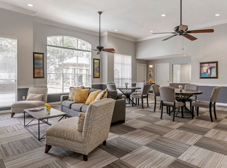 Clubhouse lounge with couch, chairs, coffee table, multi speed ceiling fans, and large windows for natural lighting