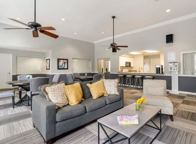 Clubhouse lounge with couch, chairs, coffee table, café style seating, carpeted flooring, and multi speed ceiling fans