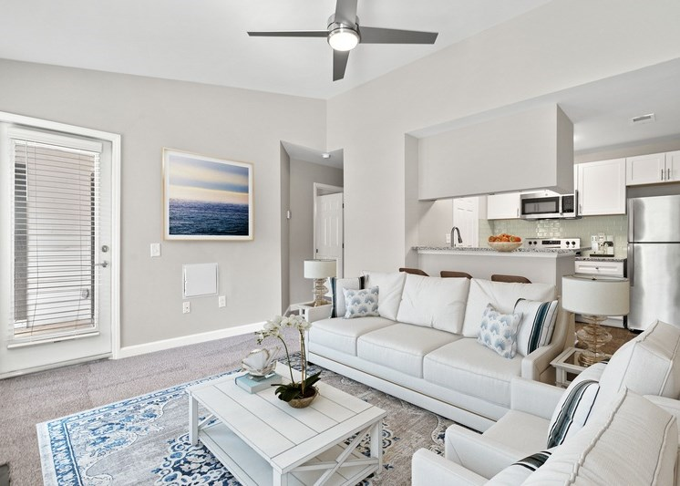 Virtual Rendering of a living room fully furnished with a white sofa, ceiling fan, and view of kitchen