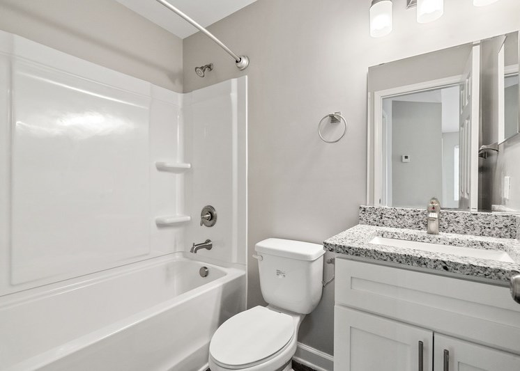 Bathroom with garden style tub, vanity lights, and white color scheme