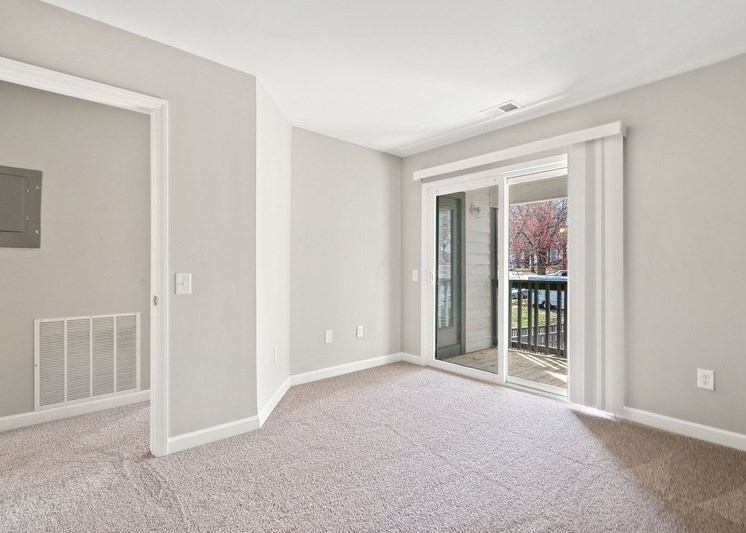 Living room with sliding patio/balcony doors, wall to wall carpet, and white walls