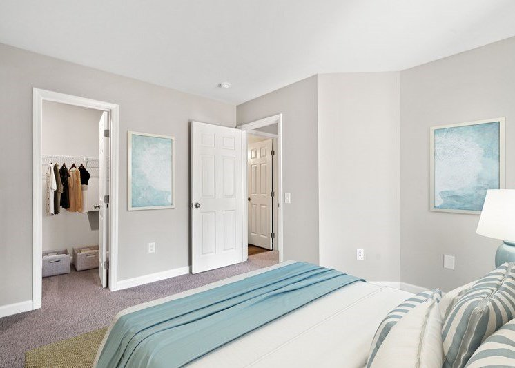 Virtual rendering of a bedroom with a white and light blue color scheme, a bed, and en-suite bathroom