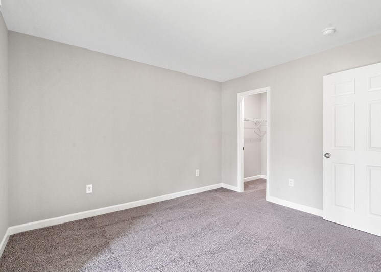 Bedroom with wall to wall carpet and white walls with white trim