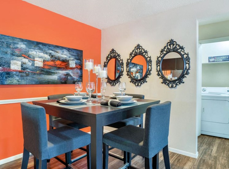 Model Dining Room with Orange Accent Wall Dining Table and Art on Walls