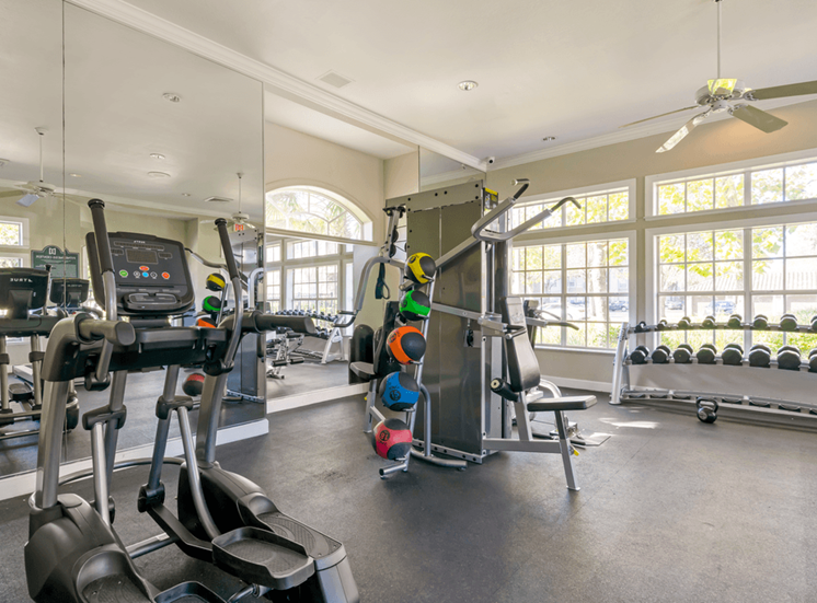 Fitness center with cardio equipment, free weights, ceiling fans, and windows for natural lighting