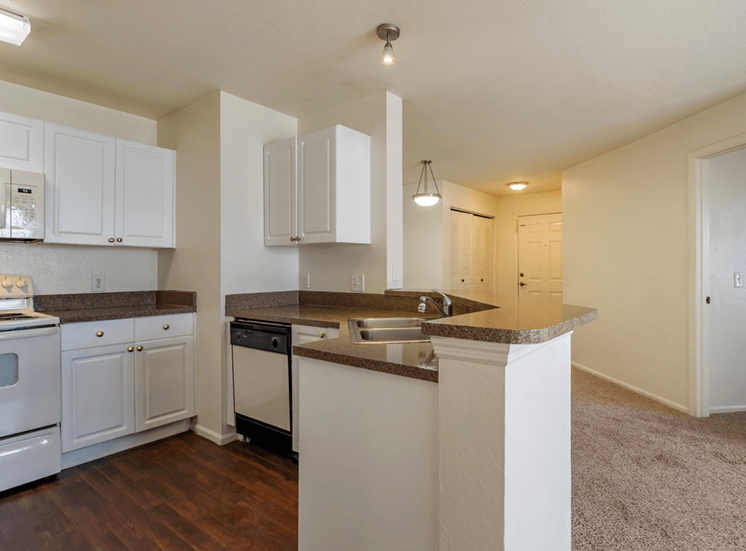 Kitchen with white appliances, hardwood style flooring, and white cabinets