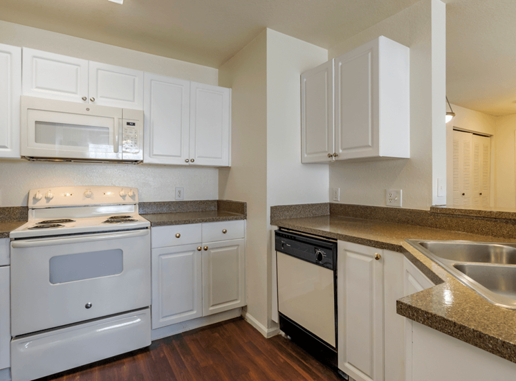 Kitchen with white appliances and hardwood style flooring
