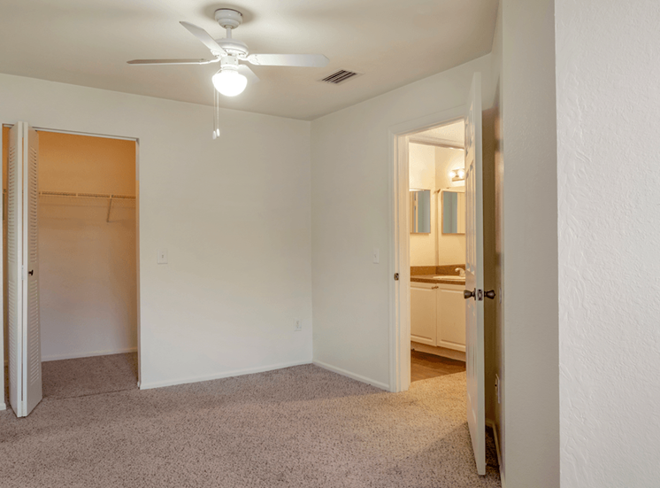 Spacious bedroom with carpet flooring, multi speed ceiling fan, and large walk-in closet