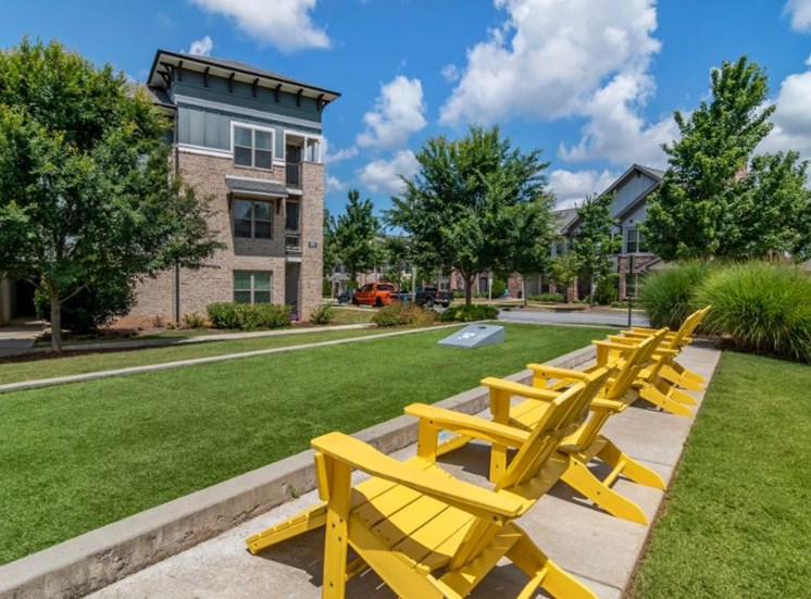 Grassy Courtyard Game Area with Yellow Lawn Chairs and Building Exteriors