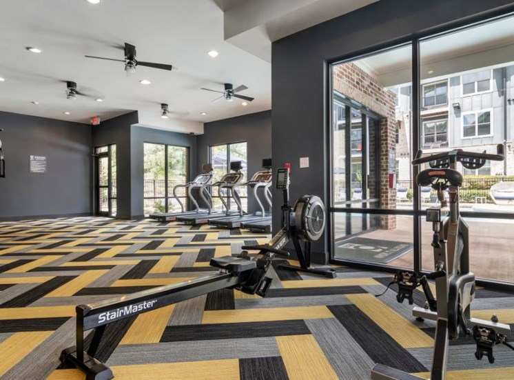 Bright Colorful Fitness Center with Mounted TV and Mirror Accent Wall