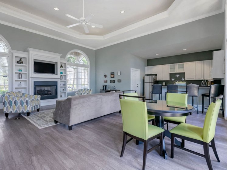 Clubhouse Seating Area with Large Windows on either side of Fireplace with TV and Shelves Surrounding Fireplace Multi Colored Accent Chairs Grey Couch Dining Table and Green Chairs and Clubhouse Kitchen with White Cabinets and Stainless Steel Appliances