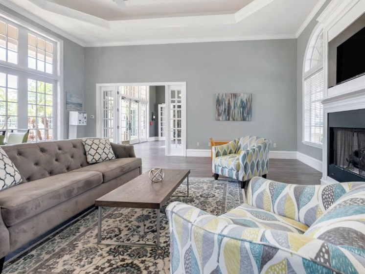 Clubhouse Seating Area with Large Windows Multi Colored Accent Chairs Grey Couch and Clubhouse Kitchen with White Cabinets and Stainless Steel Appliances