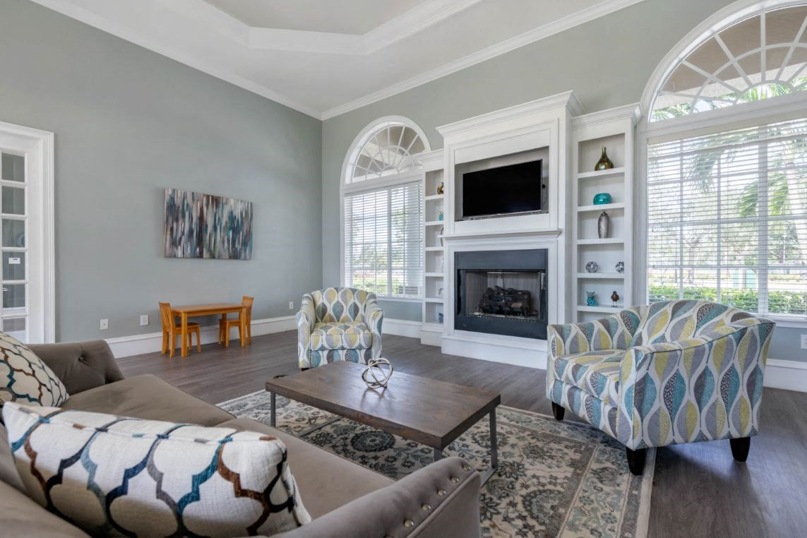 Clubhouse Seating Area with Large Windows on either side of Fireplace with TV and Shelves Surrounding Fireplace Multi Colored Accent Chairs Grey Couch and Clubhouse Kitchen with White Cabinets and Stainless Steel Appliances