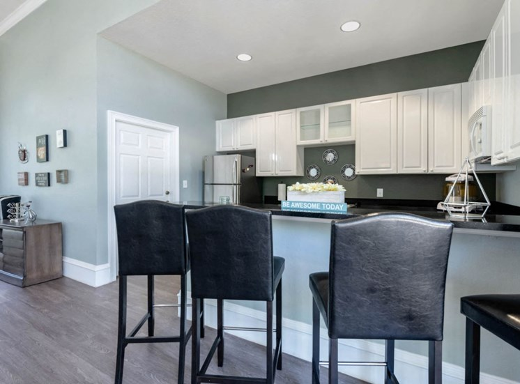 Clubhouse Kitchen with White Cabinets Black Counters Stainless Steel Appliances and Coffee Bar with Decorations