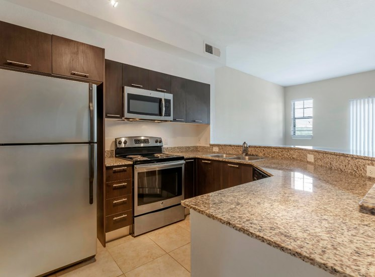 Fully equipped kitchen with stainless steel appliances, dark espresso cabinetry, tiled flooring, and wrap around breakfast bar