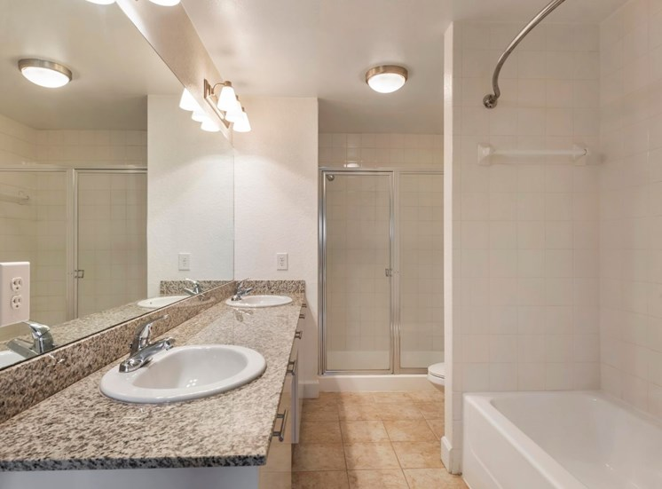 Bathroom with double sinks, vanity lighting, bath tub, and stand up shower