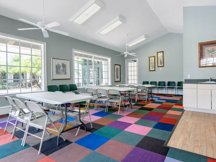 Bright Seating Area with Folding Tables and Chairs on Colorful Carpet Next to White Cabinets and Green Counters