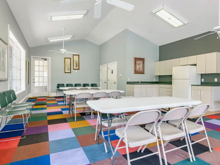 Bright Seating Area with Folding Tables and Chairs on Colorful Carpet Next to Kitchen with White Appliances and Cabinets and Green Counters