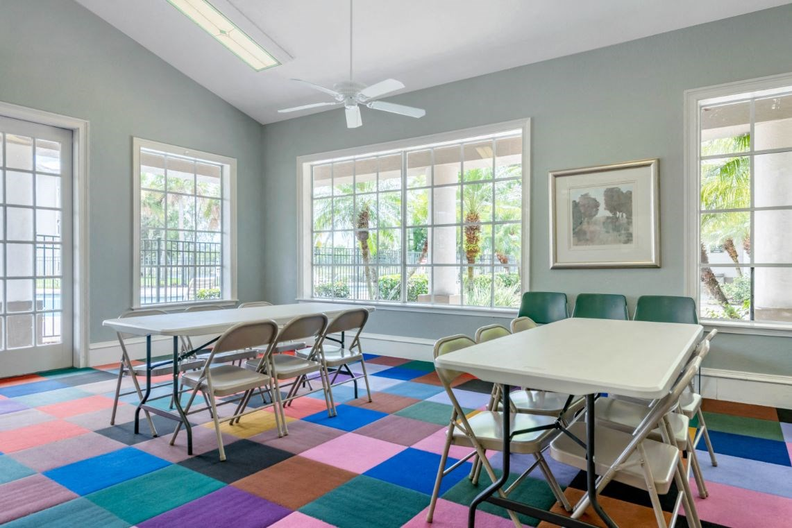 Bright Seating Area with Large Window Folding Tables and Chairs on Colorful Carpet