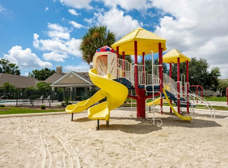Blue Red and Yellow Playground on Sand with Building Exterior and Treeline in the Background