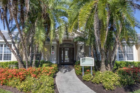 Walkway to Leasing Office Surrounded by Flowers and Palm Trees
