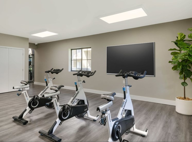 Fitness center with stationary bicycles in front of large wall mounted tv