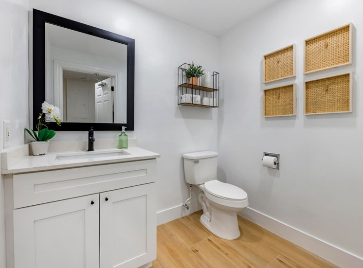 Bathroom with single vanity, white cabinets and wood style flooring