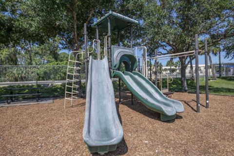 Green Playground on Mulch with Nearby Picnic Table