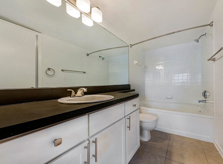 Bathroom with Spacious Black Counters, White Cabinets, and Tiled Shower with Bathtub