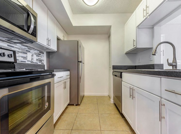Fully Equipped Kitchen with Stainless Steel Appliances, White Cabinets , Grey Counters and Glass Backsplash