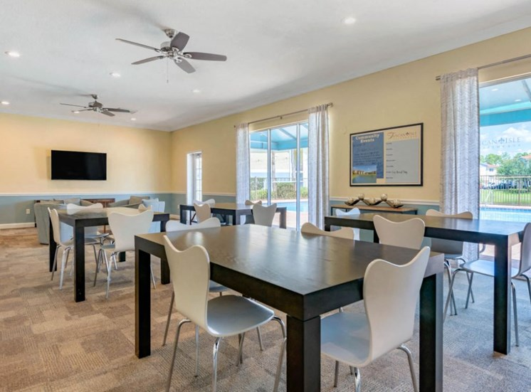 Clubhouse with Large Windows Black Tables with White Chairs Mounted TV and Ceiling Fans