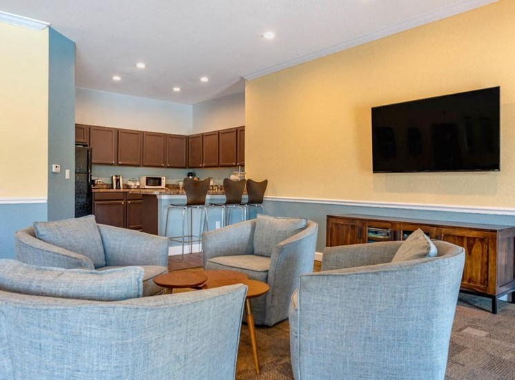 Resident Lounge Area with Mounted TV Grey Chairs Around Coffee Table and Clubhouse Kitchen with Brown Cabinets