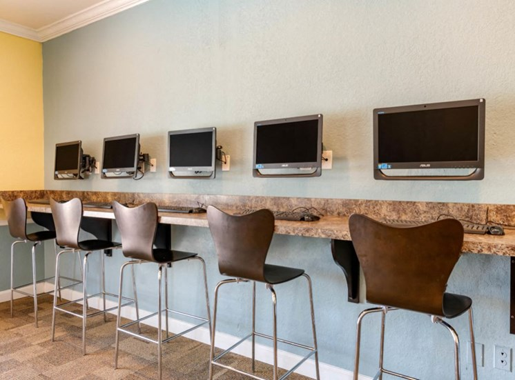 Resident Business Center with Computers Mounted to the Wall Above Bar with Brown Bar Stools