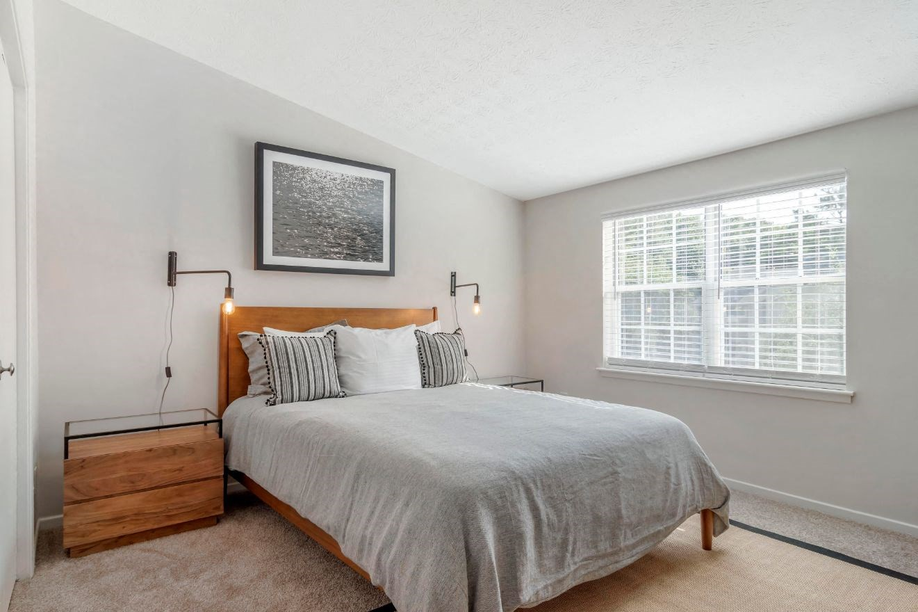 Fully Furnished Model Bedroom with Bed Under Mounted Artwork