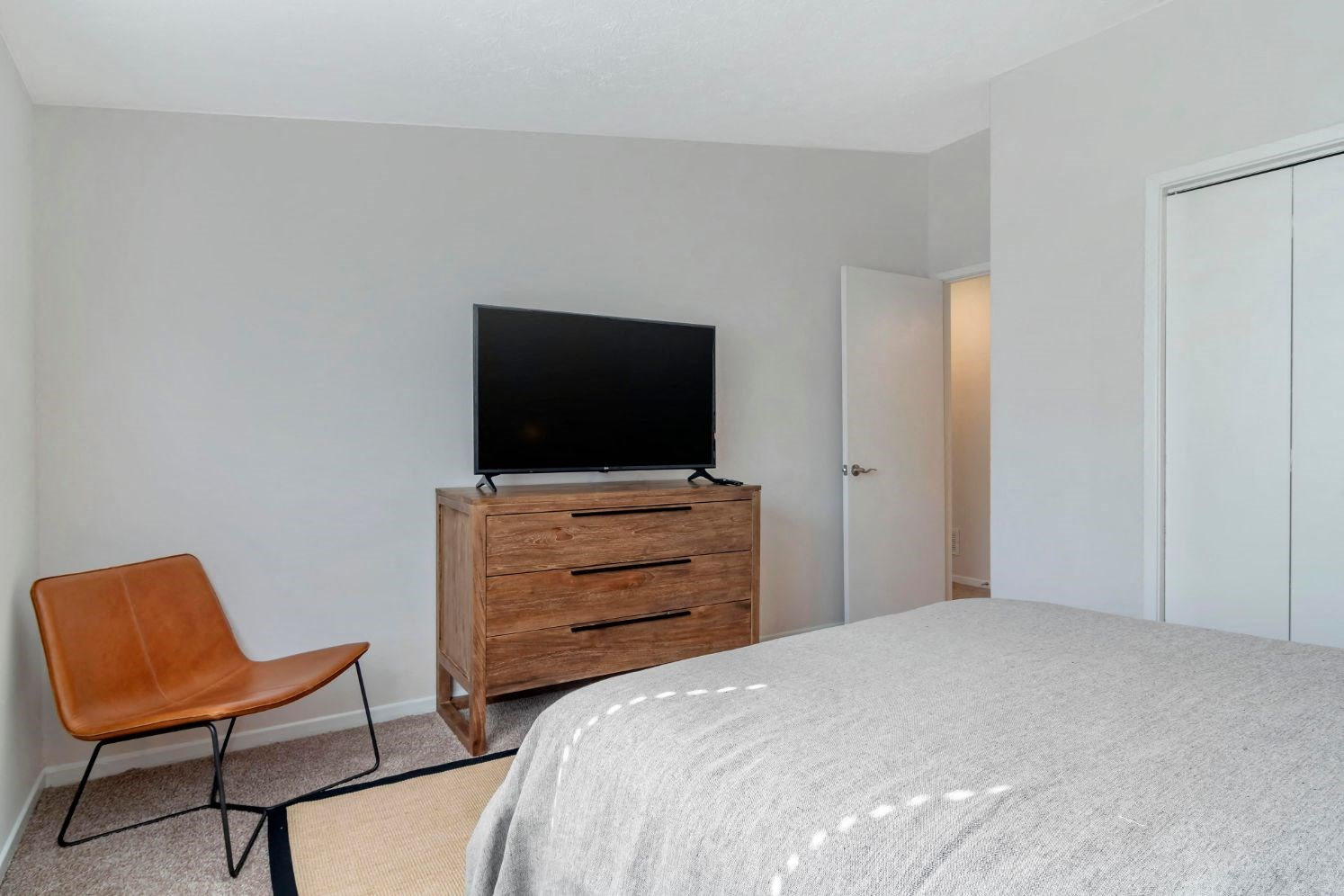 Fully Furnished Model Bedroom with Bed Dresser and TV Next Contemporary Chair