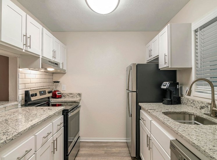 Fully Equipped Model Kitchen with White Cabinet Granite Counters and Stainless Steel Appliances