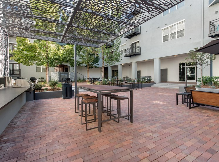 Courtyard with Summer Kitchen Under Pergola with Nearby Seating Area and Firepit Surrounded by Buildings