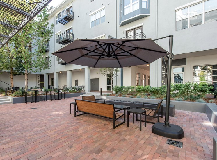 Courtyard with Brick Walkway and Patio Furniture Under Umbrella Next to Building