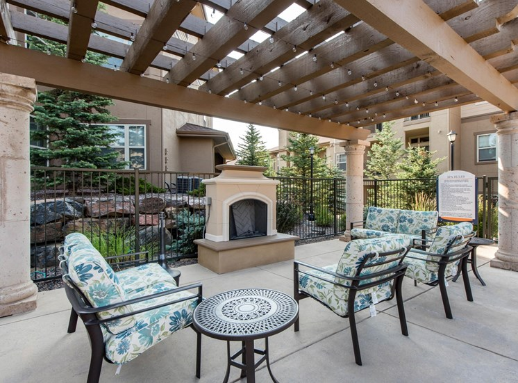 Outdoor fireplace with lounge seating under pergola