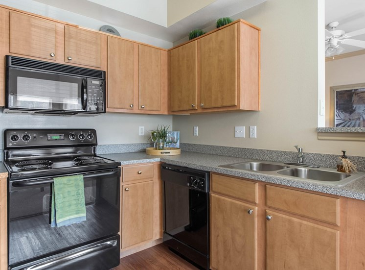 Model Kitch with Wood Cabinets, Black Appliances, Grey Counters and Decorations