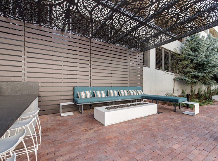 Lounge Area Under Pergola with Outdoor Sectional Next to Firepit