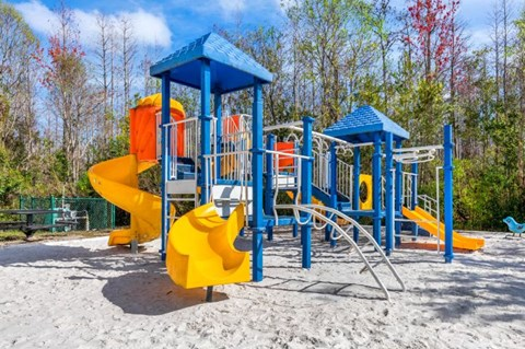 Blue and Yellow Playground on Sand with Building Exterior and Trees in the Background
