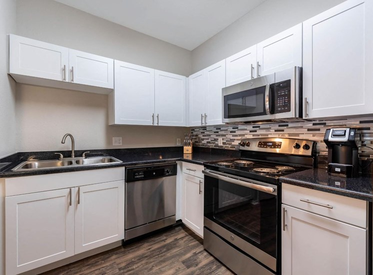 Fully equipped kitchen with stainless steel appliances, white cabinetry, double basin sink, and hardwood style flooring