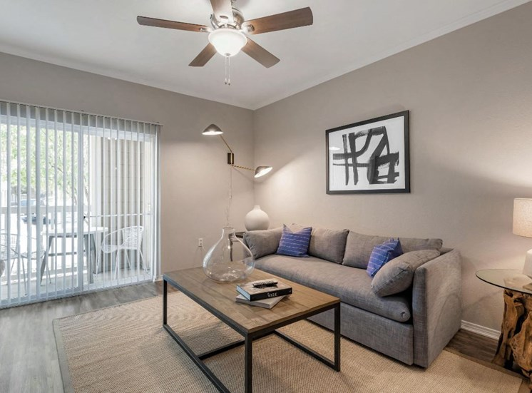 Furnished living room with couch, chair, coffee table, decorative wall art, and private balcony access