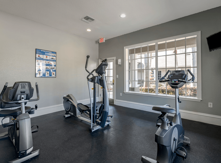 Fitness center with cardio equipment, wall mounted television, and large window for natural lighting