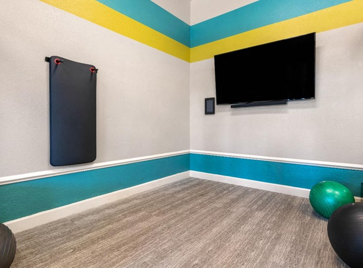 Fitness Center With Blue and Bright Green Accent Stripes with Mounted TV