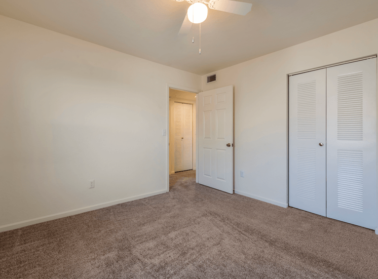 Spacious bedroom with carpet flooring, multi speed ceiling fan, and closet space
