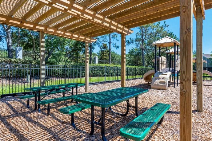 Green Picnic Tables Under Wooden Pergola Next to Fenced in Playground