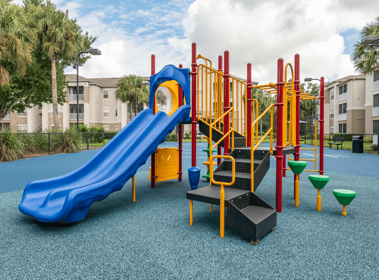Multi Colored Playground on Blue Rubber Flooring with Building Exteriors in the Background